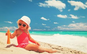 Little girl sitting on beach with sunglasses and hat holding suntan lotion