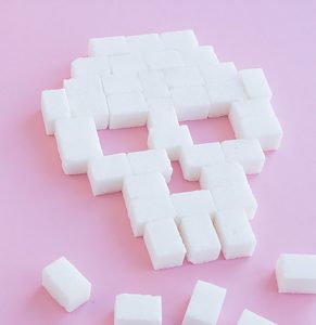 Skull made out of sugar cubes on pink background | common health myths